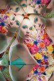 有明亮的colorfull构成的年轻美女在花背景 库存照片