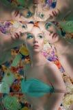 有明亮的colorfull构成的年轻美女在花背景 免版税库存图片