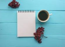有春天、分支用荚莲属的植物莓果和一杯咖啡的笔记本 明亮的蓝色,绿松石表面 特写镜头拷贝空间 库存图片