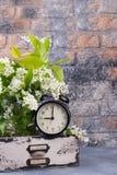 有春天开花的分支的闹钟在反对砖墙背景的木抽屉 免版税库存照片