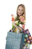 有春天郁金香和购物的礼品袋子花束的愉快的微笑的女孩。 库存图片