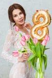 有春天郁金香的美丽的少妇开花花束 微笑举行的愉快的女孩开花,桃红色郁金香 春天画象 库存图片