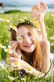 有春黄菊花圈的逗人喜爱的儿童女孩  免版税库存图片