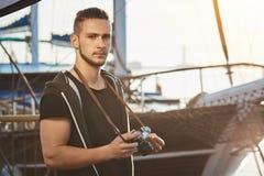 有是时髦的理发的英俊的确信的人站立在令人敬畏的游艇附近,拿着照相机,严重凝视和 免版税图库摄影