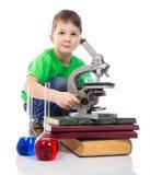 有显微镜的感兴趣的小男孩 图库摄影