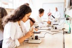 有显微镜的美丽的高中学生在实验室 免版税库存图片