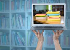 有显示书堆的膝上型计算机的手反对有蓝色覆盖物的模糊的书架 库存照片