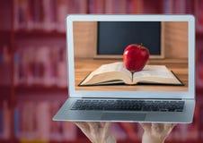 有显示书用红色苹果的膝上型计算机的手反对有红色覆盖物的模糊的书架 免版税库存照片