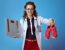 有显示健身运动鞋的重量标度的医师妇女 库存照片