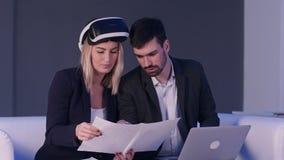 有显示图纸的VR耳机的女性建筑师对她的使用膝上型计算机的男性同事 库存照片