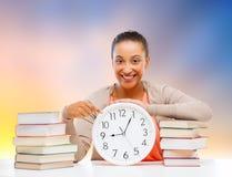 有显示在时钟的书的学生女孩时间 免版税库存照片