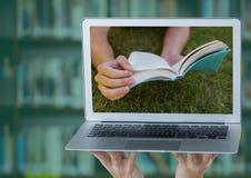 有显示在草的膝上型计算机的手书反对有绿色覆盖物的模糊的书架 图库摄影