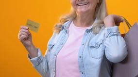 有显示在黄色背景的购物带来的愉快的退休的夫人金卡片 影视素材