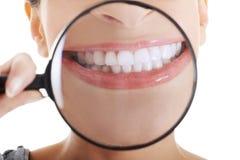 有显示她完善的白色的放大镜的美丽的妇女 免版税图库摄影