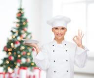 有显示好标志的空的板材的女性厨师 免版税库存照片