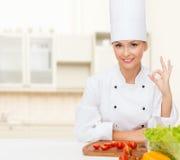 有显示好标志的菜的女性厨师 库存照片