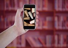 有显示常设书的电话的手反对有红色覆盖物的模糊的书架 免版税库存照片