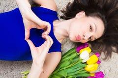 有显示心脏标志用手的花的快乐的深色的白种人女孩 库存图片