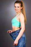 有显示成功的减重的大牛仔裤的亭亭玉立的妇女 库存照片