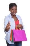 有显示拇指的购物袋的可爱的非洲妇女 库存图片