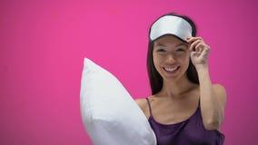 有显示沈默标志和戴着眼罩的枕头的亚裔夫人,准备好睡觉 股票录像