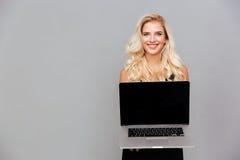有显示空白的便携式计算机屏幕的长的头发的白肤金发的妇女 库存照片