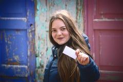 有显示空白的名片的大微笑的少妇 浅景深,在卡片的焦点 免版税库存图片