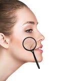 有显示老化皮肤的放大镜的妇女 免版税库存照片