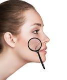 有显示老化皮肤的放大镜的妇女 库存图片