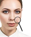 有显示老化皮肤的放大镜的妇女 图库摄影