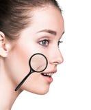有显示老化皮肤的放大镜的妇女 库存照片