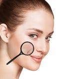 有显示老化皮肤的放大镜的妇女 免版税图库摄影