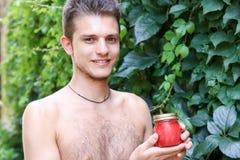 有显示西红柿酱的赤裸躯干的英俊的年轻人 免版税图库摄影