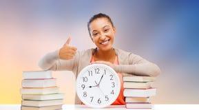 有显示赞许的书和时钟的学生 库存照片