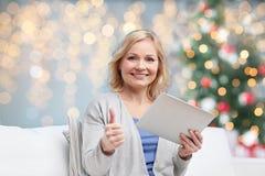 有显示赞许的片剂个人计算机的愉快的妇女 免版税库存图片