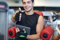 有显示赞许的片剂个人计算机的年轻人在健身房 免版税库存图片