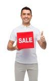 有显示赞许的红色销售叹气的微笑的人 免版税库存照片
