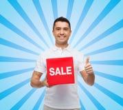 有显示赞许的红色销售叹气的微笑的人 库存照片