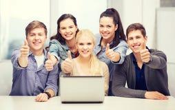 有显示赞许的膝上型计算机的微笑的学生 免版税库存图片