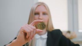 有显示赞许的bitcoin的愉快的女性 微笑的快乐的白肤金发的妇女在办公室在工作场所适合坐与 股票视频