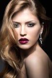 有晚上构成、红色嘴唇和卷毛的美丽的妇女 秀丽表面 免版税库存照片