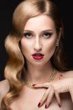 有晚上构成、红色嘴唇和卷毛的美丽的妇女 秀丽表面 免版税库存图片