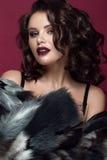 有晚上构成、黑暗的嘴唇和长的卷毛头发的美丽的妇女 注视发烟性 床单方式放置照片诱人的白人妇女年轻人 库存图片