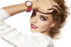 有晚上构成红色嘴唇和手表的美丽的女孩 免版税库存照片