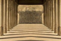 有晚上阴影和砖块的古老对称走廊 免版税库存照片