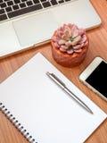 有智能手机、手提电脑和多汁植物的空白的笔记本在木桌背景的铜罐的 库存图片
