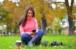 有智能手机、照相机和外带的咖啡的年轻时兴的十几岁的女孩在秋天开会和微笑的公园 免版税库存照片