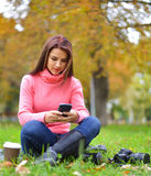 有智能手机、照相机和外带的咖啡的年轻时兴的十几岁的女孩在秋天开会和微笑的公园 库存图片