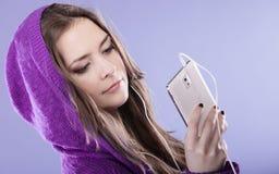 有智能手机听的音乐的青少年的女孩 免版税库存图片