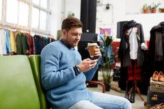 有智能手机和咖啡的人在服装店 免版税库存照片